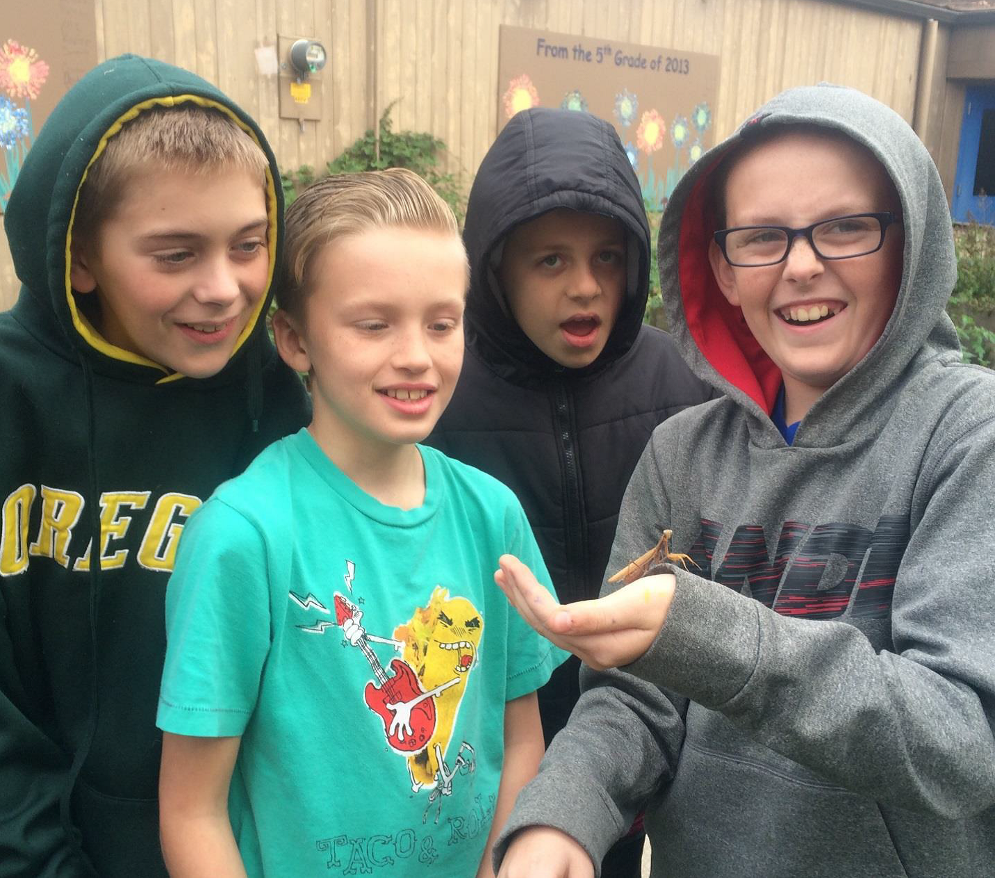 Clear Lake 5th graders with their new friend, a praying mantis found in their school garden.