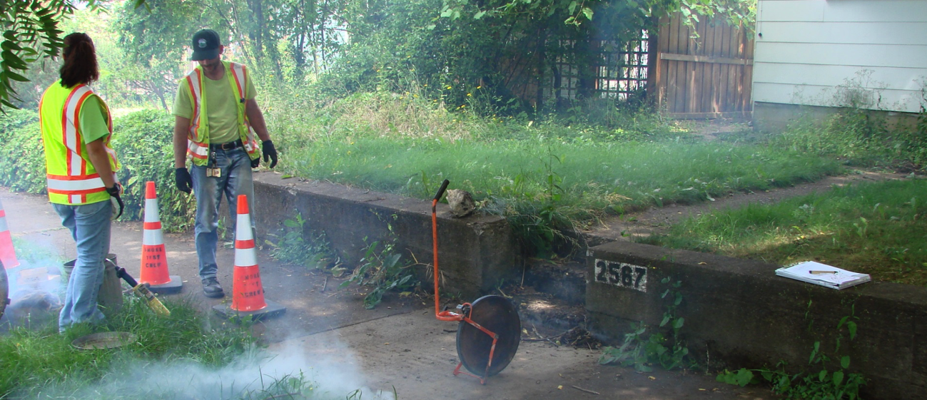 Worker performing a smoke test of Eugene wasterwater line