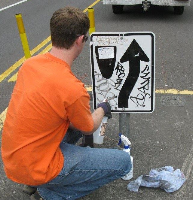 Employee removing graffiti from a sign