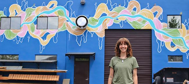 Erica Greminger in front of mural