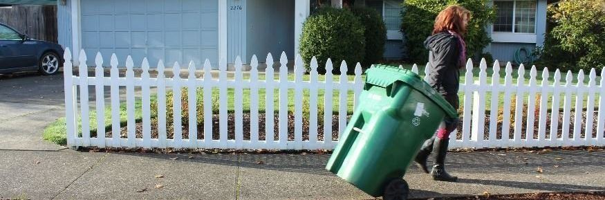 A Eugene resident removing a recycling bin from the curb