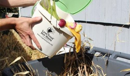 hands placing food waste into a yard waste bin-links to info about residential food waste collection