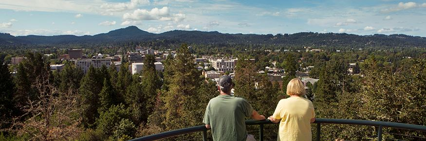 Two people looking at Eugene skyline from Skinner's Butte