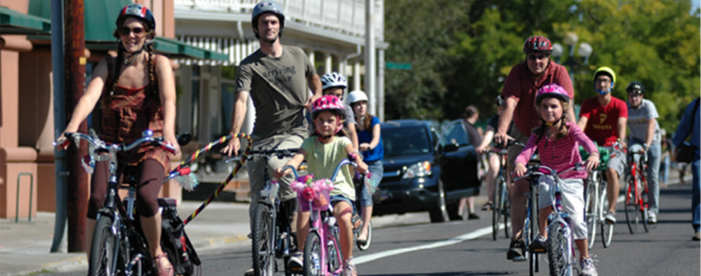 Riders of all ages enjoying biking down the car-free streets at Eugene Sunday Streets