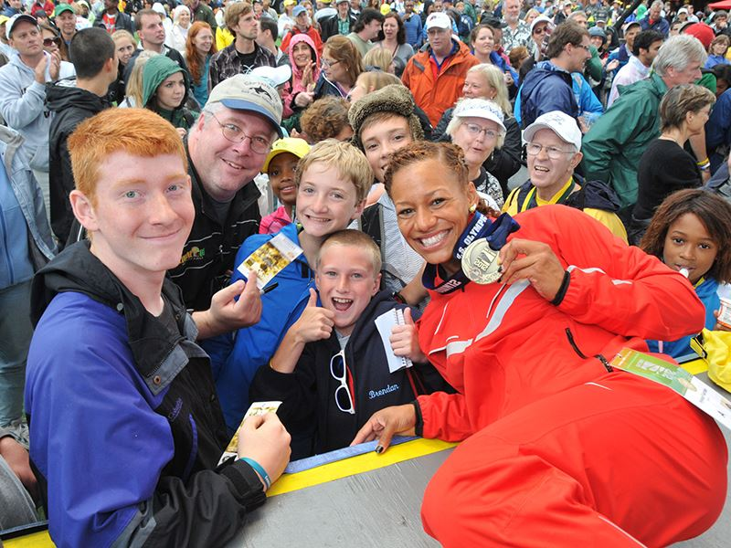 Track athlete posing with fans and showing off her medal.